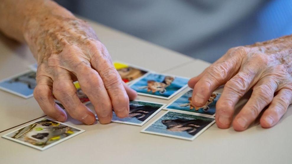 Hände einer alten Frau, die Memory-Karten nebeneinander legt.