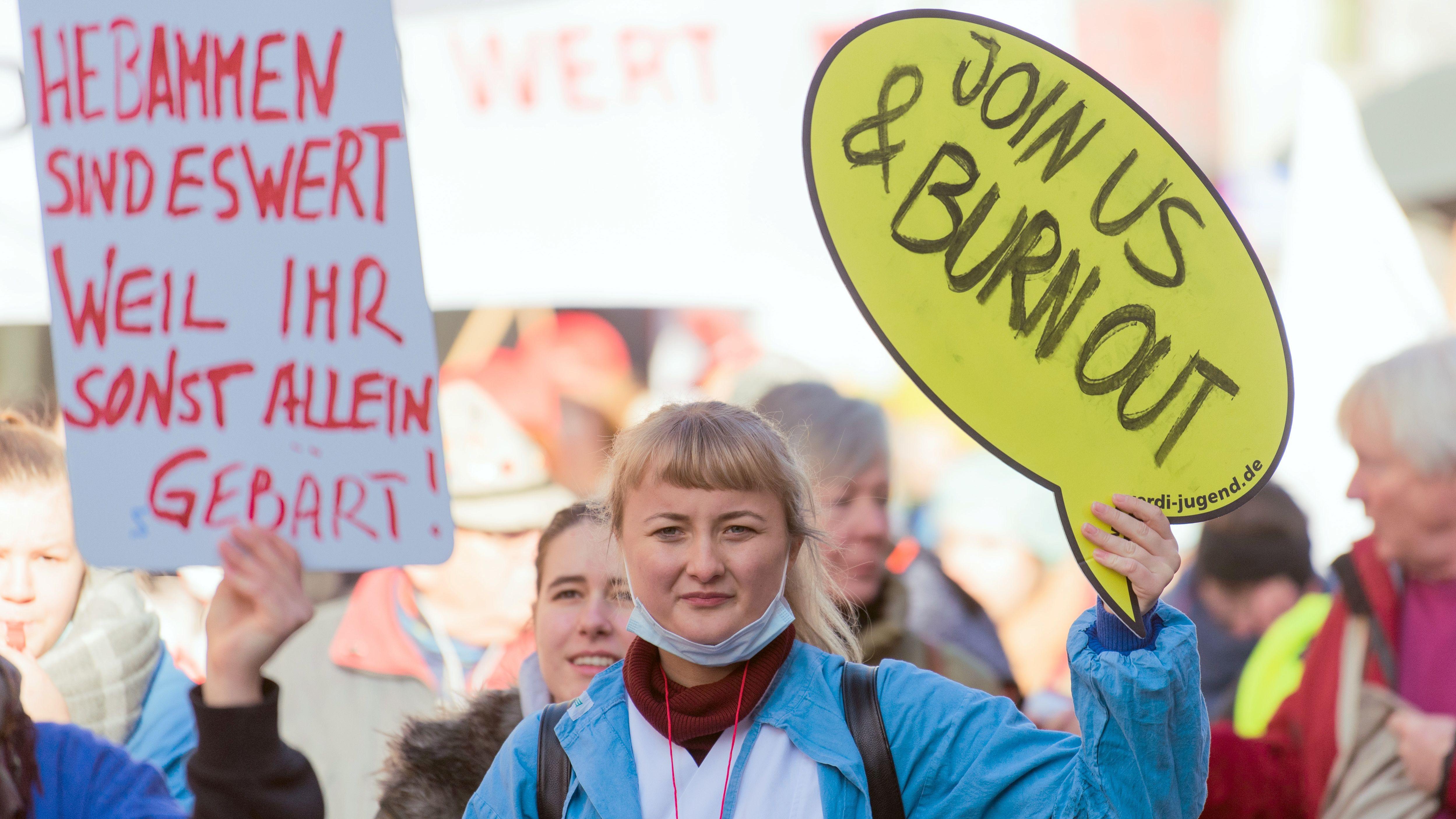 """Pflegekräfte während eines Warnstreiks im Februar 2019 in Würzburg, auf einem Schild steht: """"Hebammen sind es wert, weil ihr sonst allein gebärt"""""""