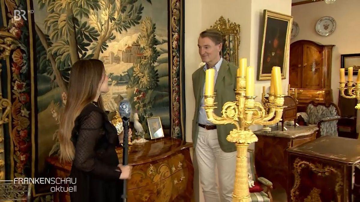 Zwei Menschen stehen sich gegenüber in einem Raum mit viel alten Möbeln.
