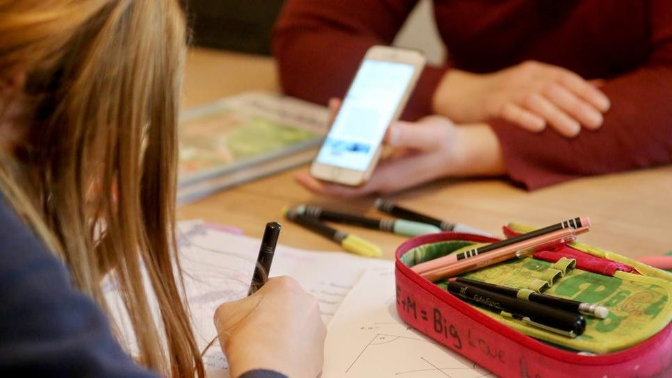 Ein Mädchen sitzt an einem Tisch über ihr Heft mit Matheaufgaben gebeugt.