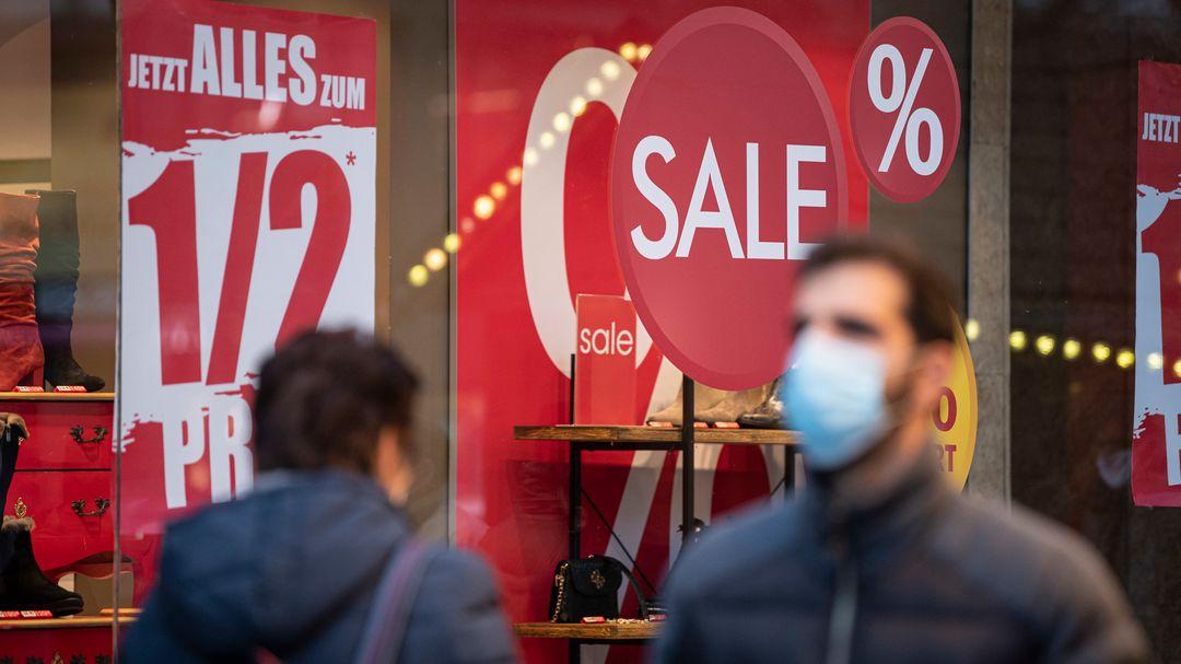 Kunden laufen mit Masken an einem Geschäft vorbei.