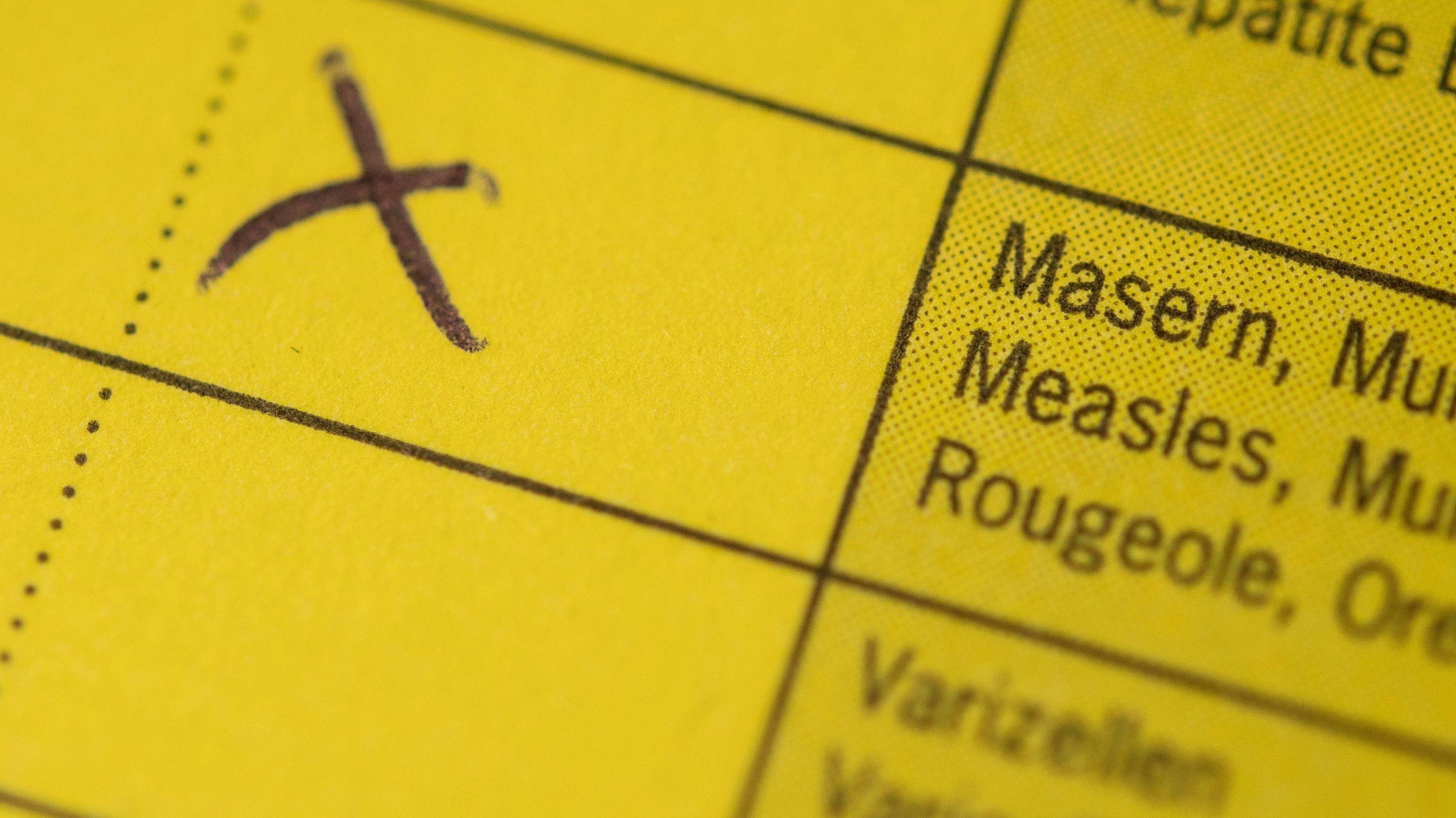 Ein Impfpass mit der Spalte für die Masernschutzimpfung und einem Kreuz