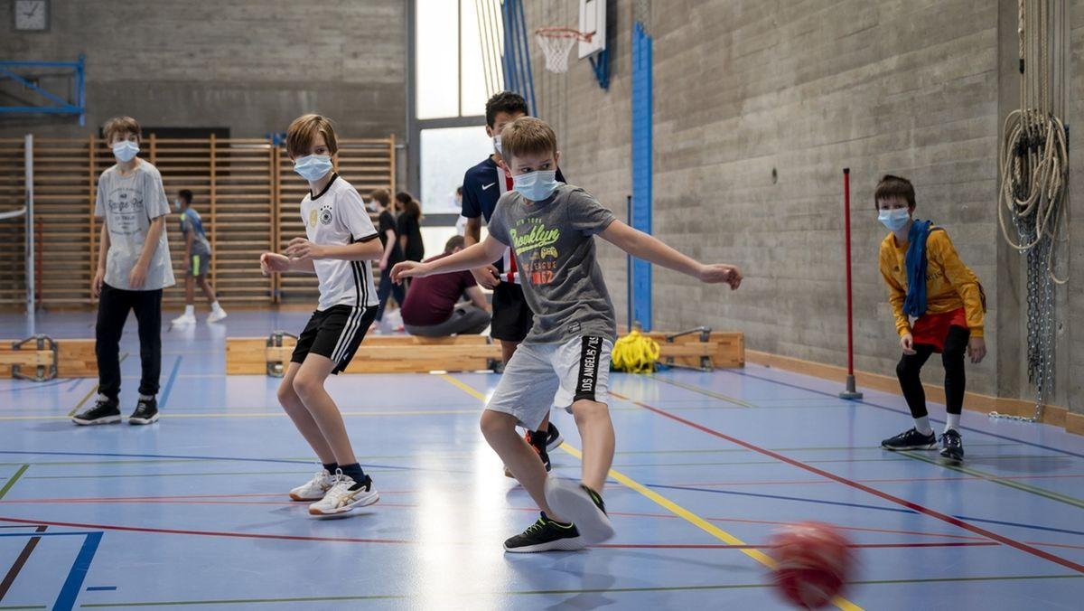Kinder spielen Fußball in der Halle mit Maske