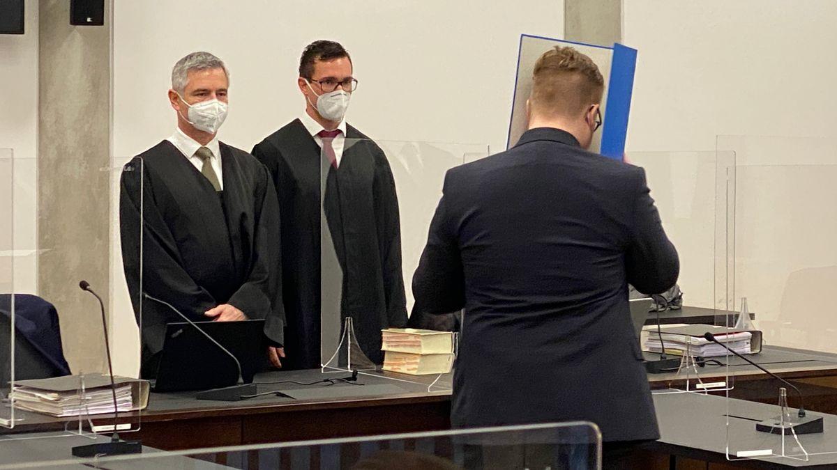 Der Angeklagte, der sich einen Ordner vors Gesicht hält, im Gerichtssaal zusammen mit seinen beiden Anwälten.