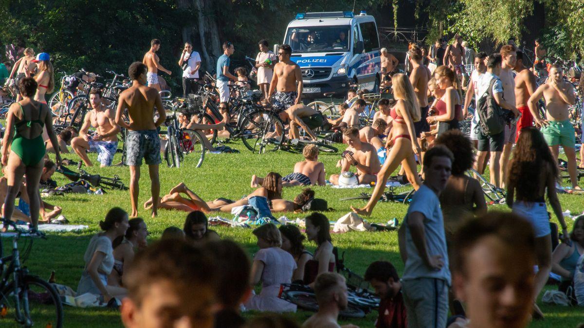 20.08.2020, Bayern, München: Sonnenhungrige bevölkern die Wiesen im Englischen Garten, während ein Polizeiwagen vorbeifährt.