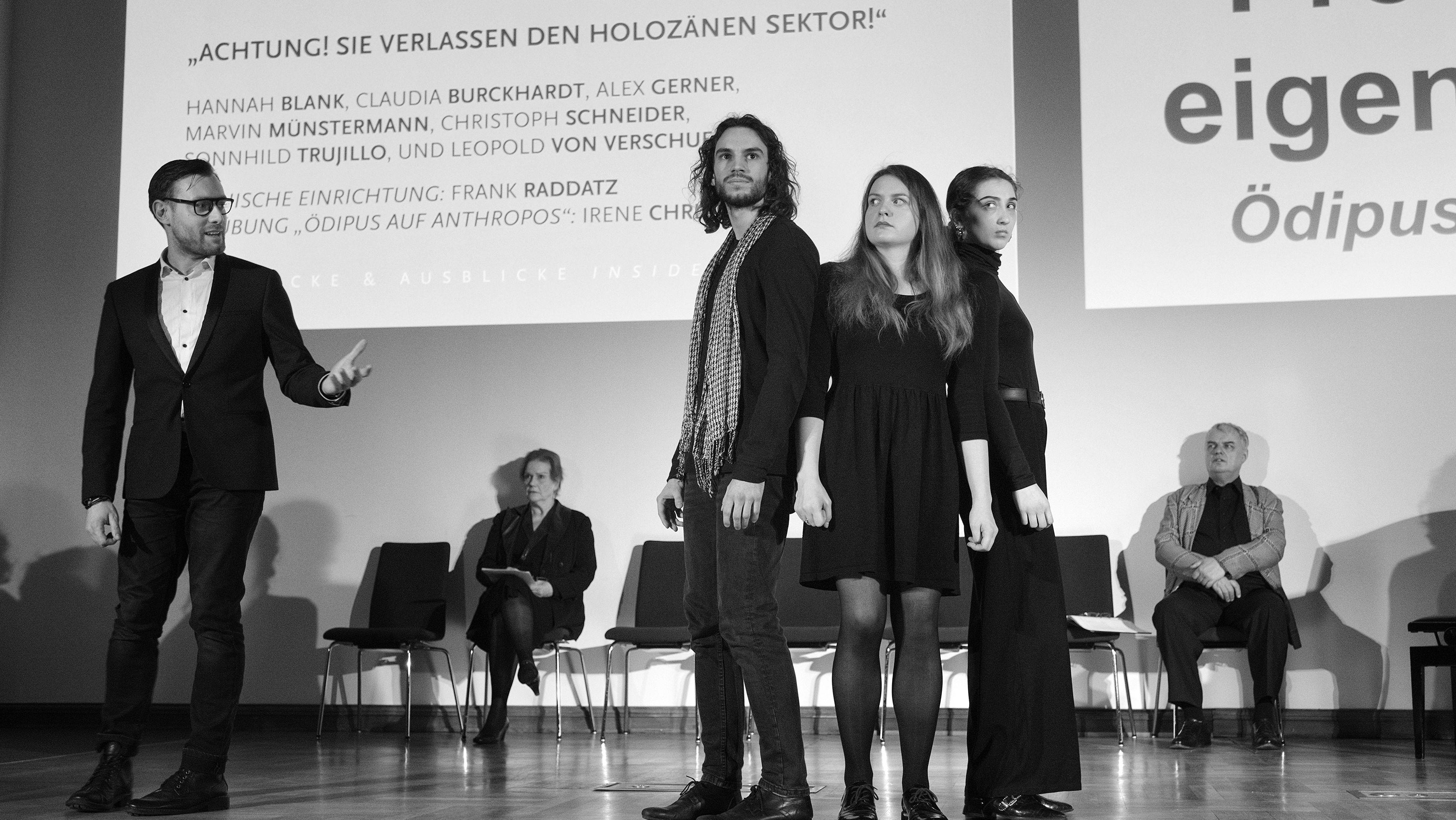 Schwarzweißaufnahme einer Bühne, auf der im Vordergrund 2 Frauen und 2 Männer stehen, im Hintergund einige auf sühtlen sitzen.