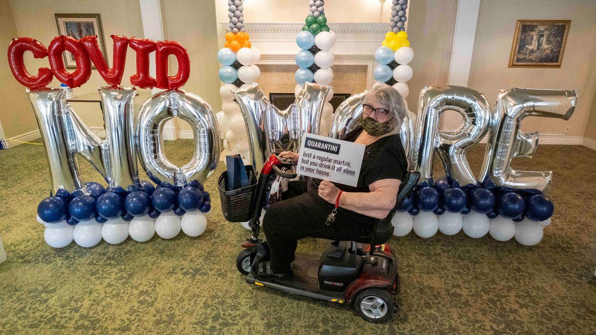 """Marylin Short sitzt auf einem Elektomobil vor Luftballons, die den Schriftzug """"Covid- No More"""" (Kein Corona mehr) bilden, nachdem sie während einer """"Bye Bye Corona""""-Impfparty im Seniorenheim Aegis Living geimpft wurde."""