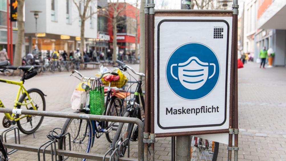 Ein Schild der Stadt Erlangen weist auf die geltende Maskenpflicht hin.
