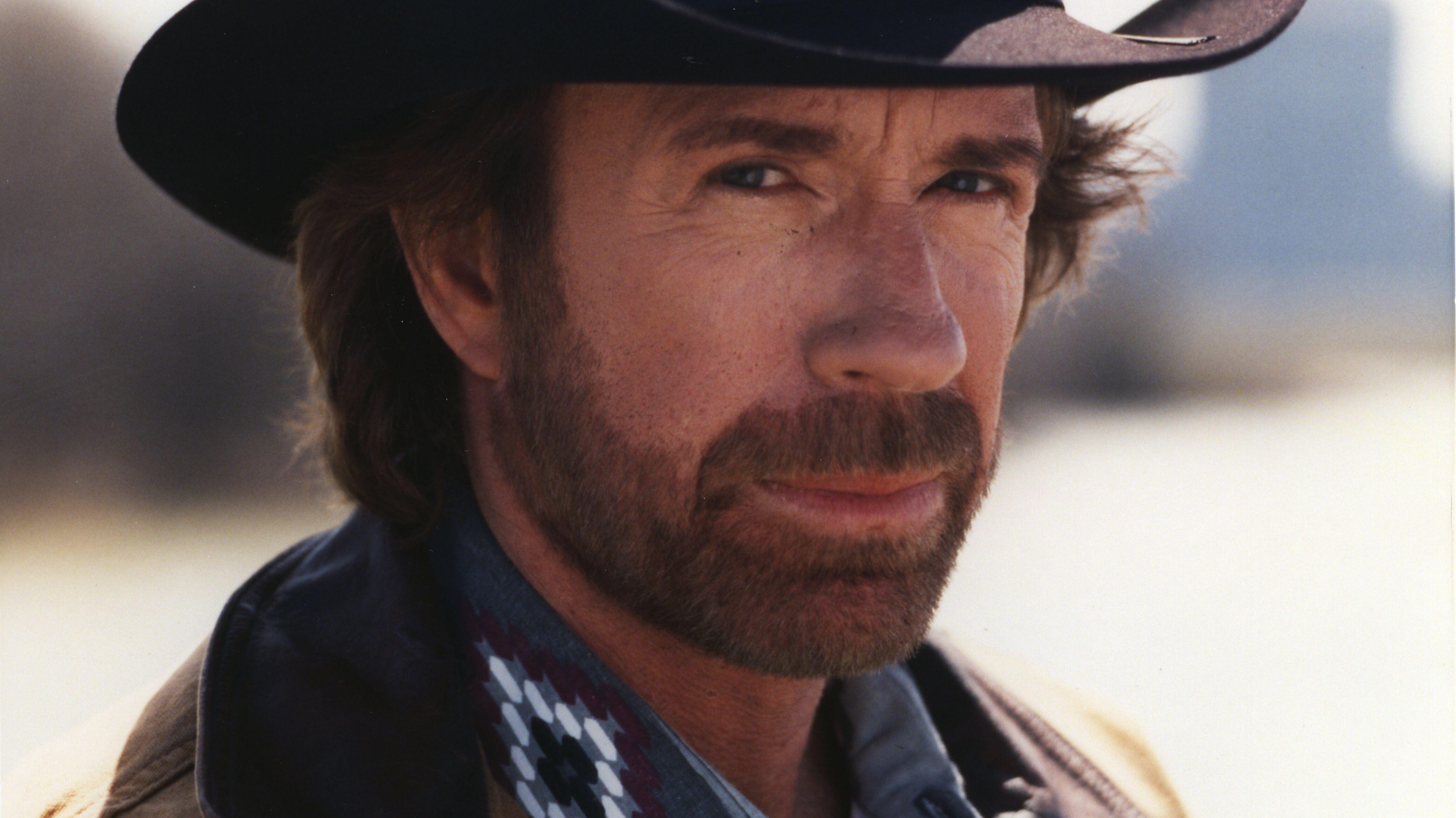 Chuck Norris, mit Vollbart und Cowboyhut, blickt stahlhart in die Kamera