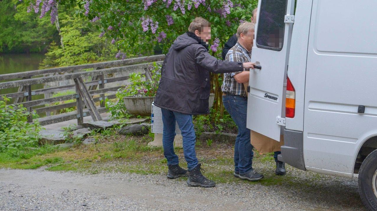 Ermittler laden Beweismittel in ihr Auto vor der Passauer Pension