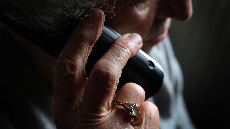 Eine ältere Frau telefoniert mit einem schnurlosen Telefon.