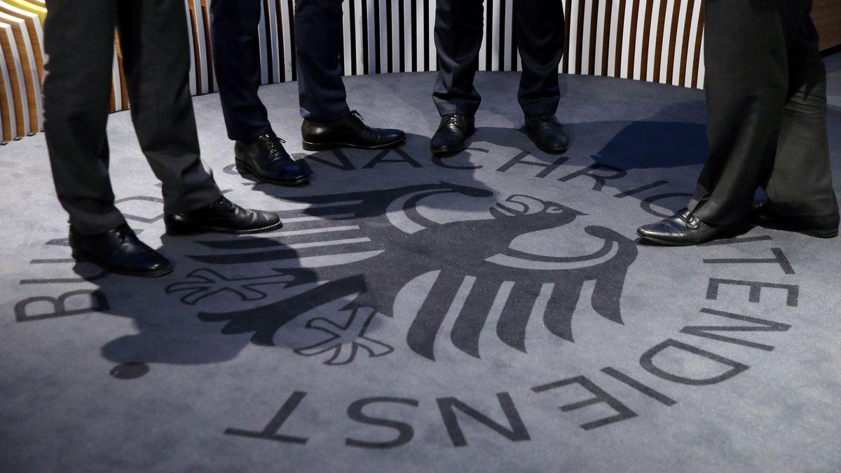 Männerbeine in schwarzen Anzughosen und Lederschuhe stehen auf dem Logo des Bundesnachrichtendienstes