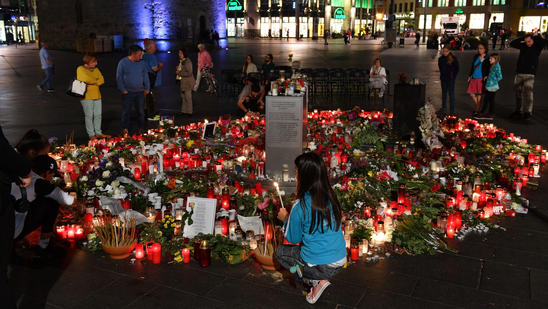 Menschen kommen nach einem ökumenischen Gedenkgottesdienst für die Opfer des Terroranschlags in Halle vor der Marktkirche in Halle/Saale zusammen und stellen Kerzen ab.