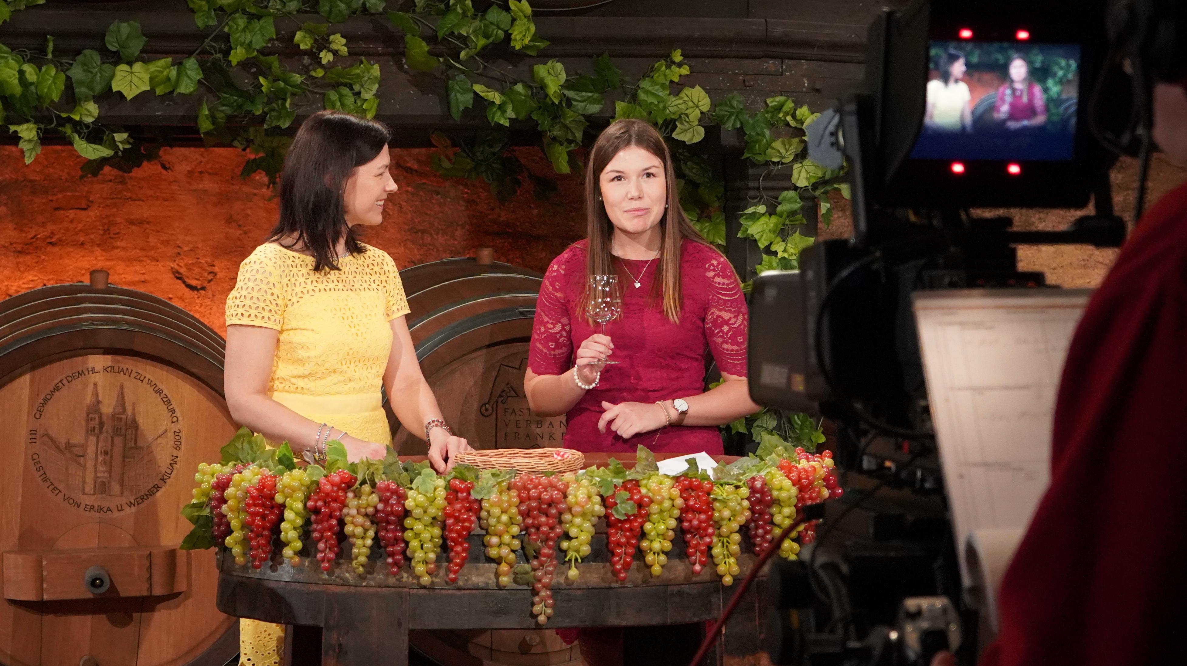 Zwei Frauen - eine hält ein Weinglas in der Hand