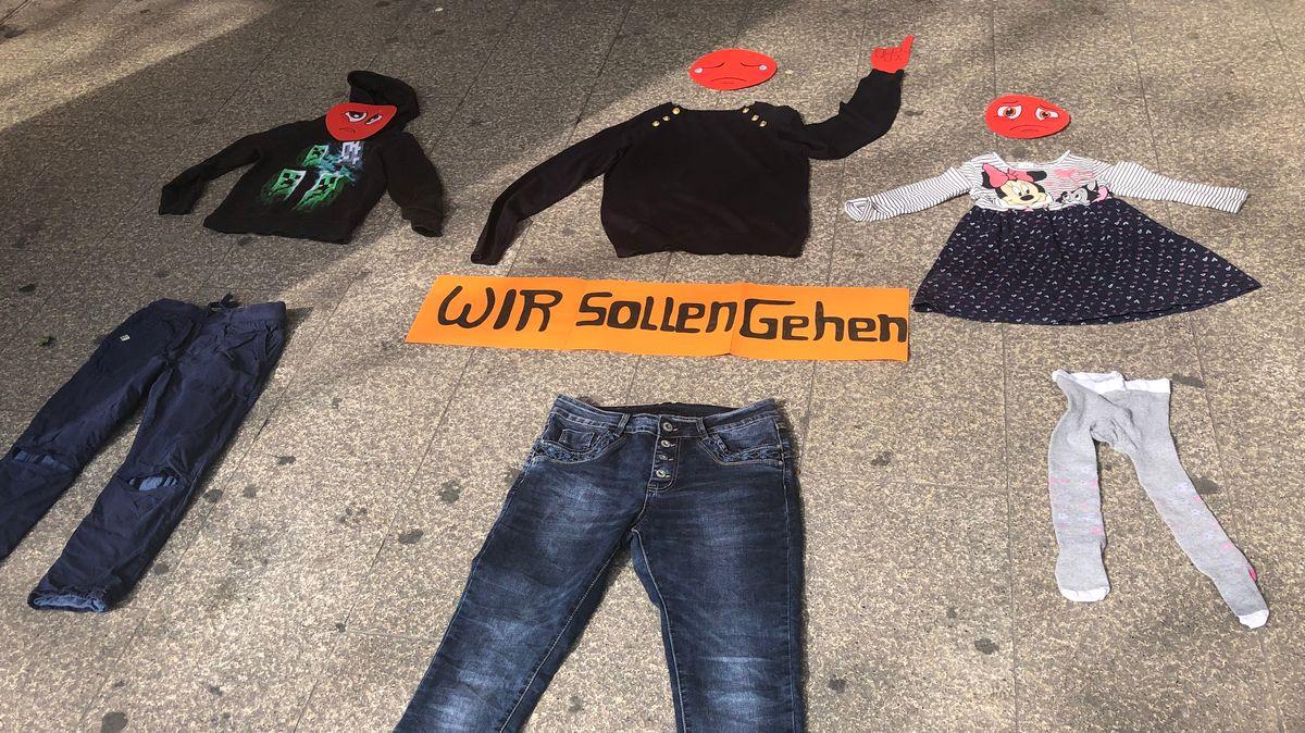 Zu Figuren drapierte Kleidung und weinende Smileys auf dem Gehweg vor dem Rosenheimer H&M