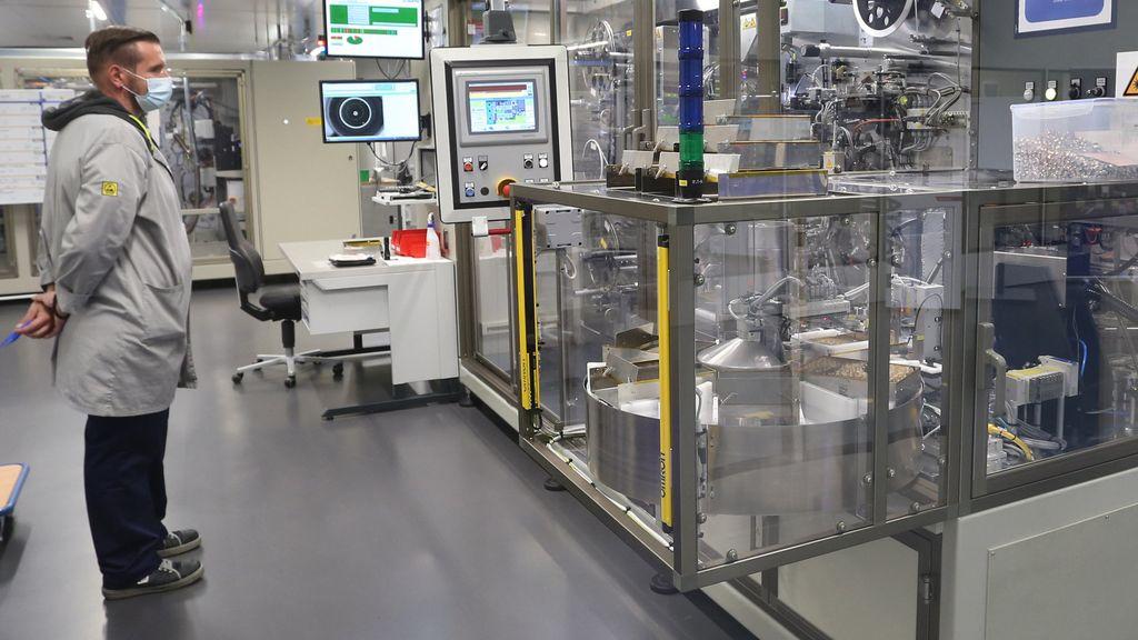 Ein Mitarbeiter steht in einen Reinraum für die Produktion von Knopfzellen in der Lithium-Ionen-Fabrik von Varta.