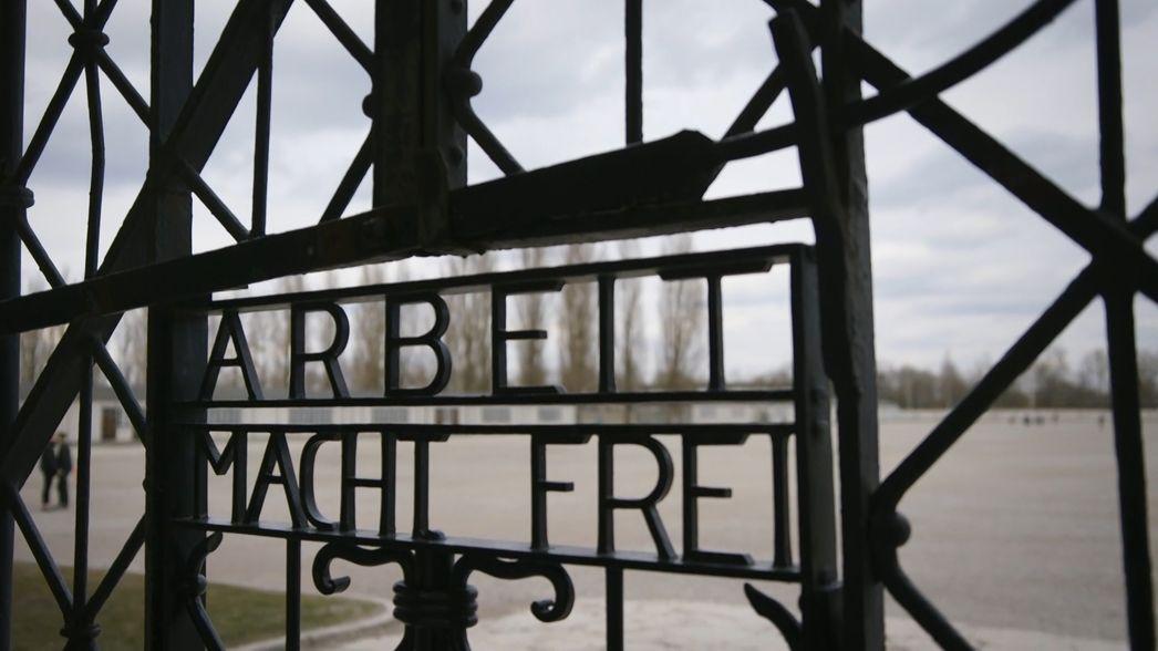 """Eingang der KZ-Gedenkstätte Dachau. Zu lesen ist der Schriftzug """"Arbeit macht frei""""."""