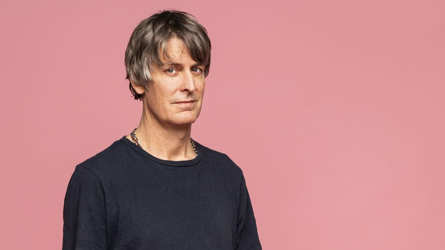 US-Songwriter Stephen Malkmus steht im dunklen T-Shirt vor einer rosafarbenen Wand