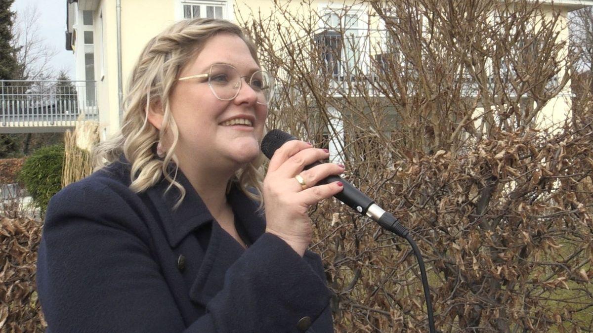 Kristina Rothbucher singt mit Mikrofon in der Hand