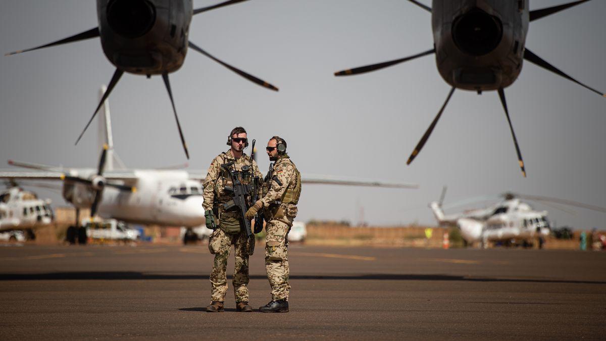 Deutsche Soldaten stehen am Flughafen in Gao und sichern ein Transportflugzeug.
