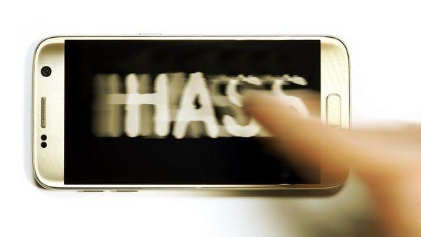 """Ein unscharfer Finger zeigt auf ein I-Phone auf dem in Großbuchstaben """"Hass"""" steht"""