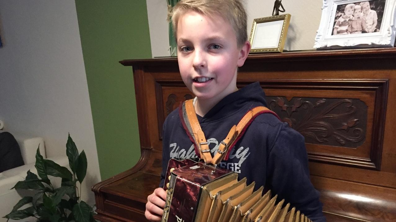 Ein Junge hält ein Akkordeon.