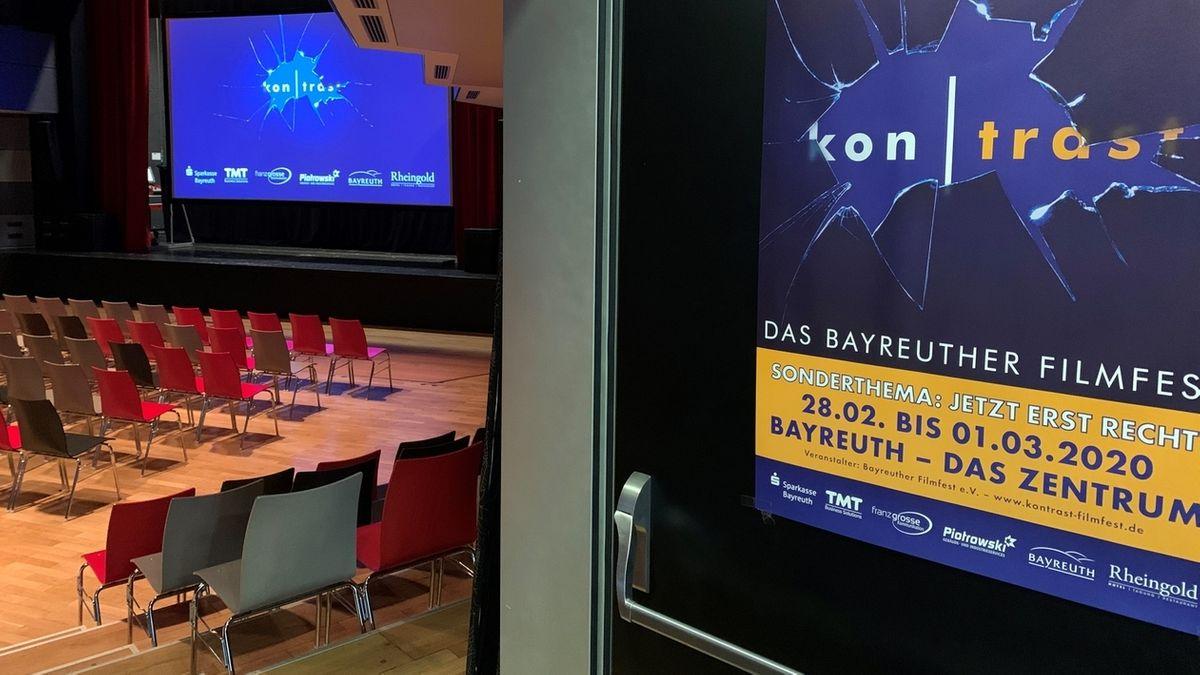 """In einem leeren bestuhlten Saal werden auf einem Poster und einer Leinwand das Bayreuther Filmfest """"Kontrast"""" beworben"""