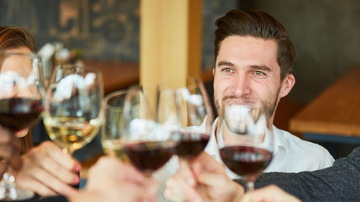 Junger Mann beim Anstoßen mit einem Glas Wein mit Freunden im Restaurant. (Symbolbild)