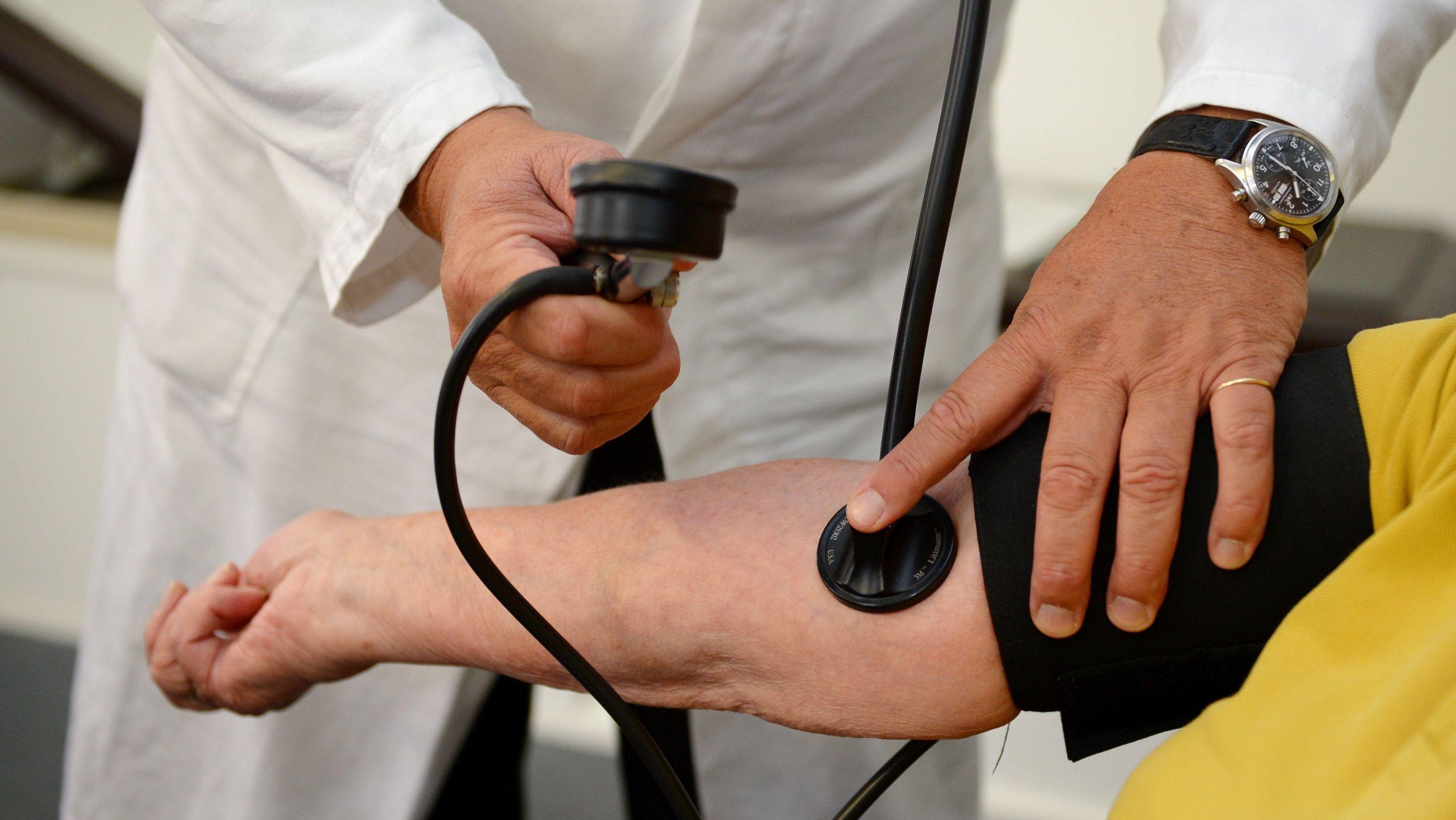 Ein Arzt misst in einer Praxis einer Patientin den Blutdruck