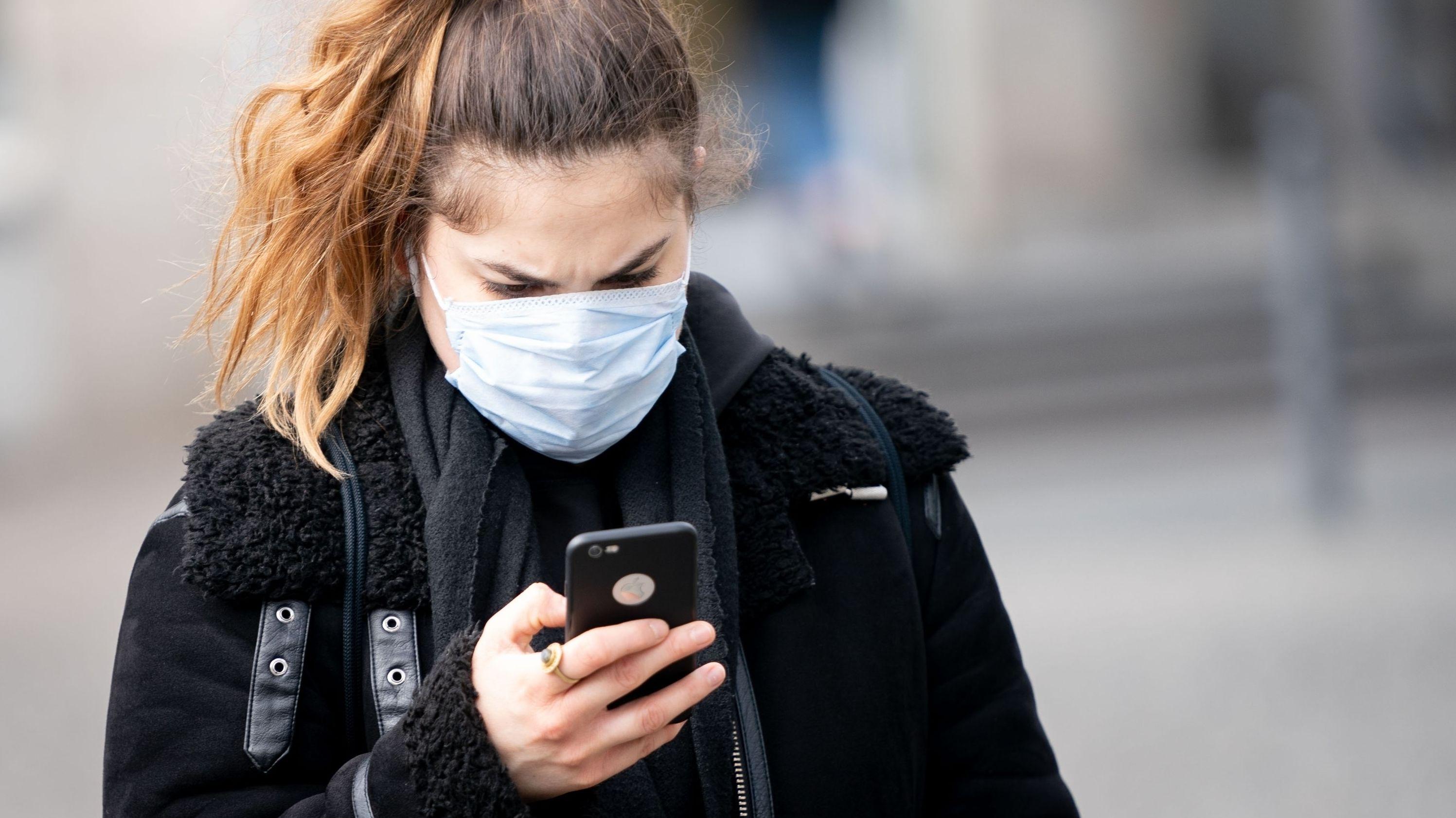 Eine Frau mit einer Mund-Nasen-Maske blickt auf ihr Smartphone.