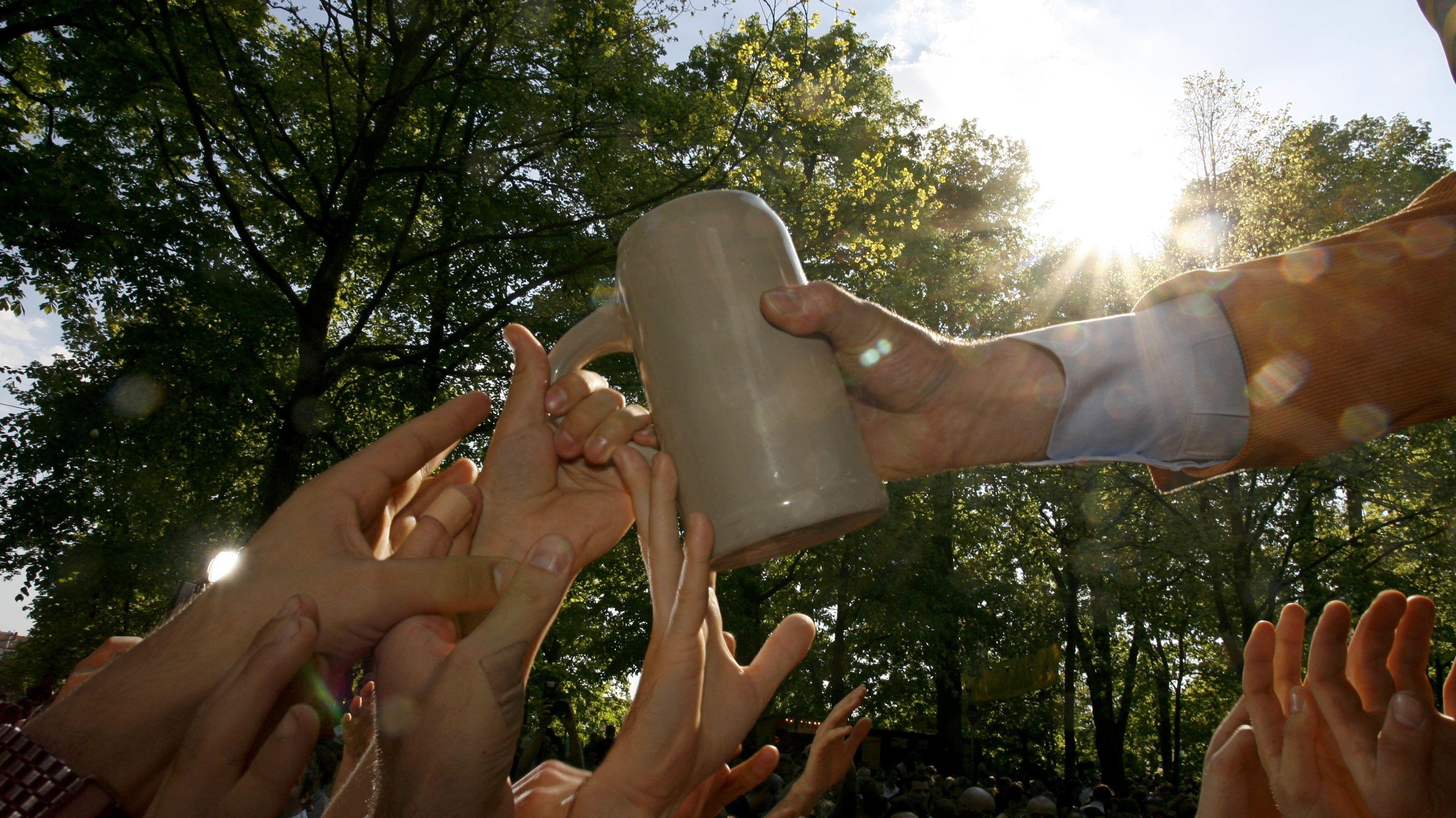 Viele Hände greifen nach einem Krug Bier.