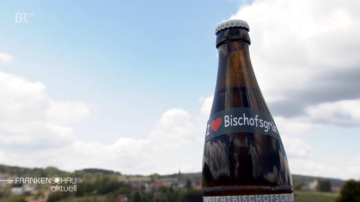 """Eine Flasche Bier, auf dessen Etikett """"I Love Bischofsgrün"""" (Ich liebe Bischofsgrün"""") zu lesen ist, im Hintergrund der Ort Bischofsgrün."""