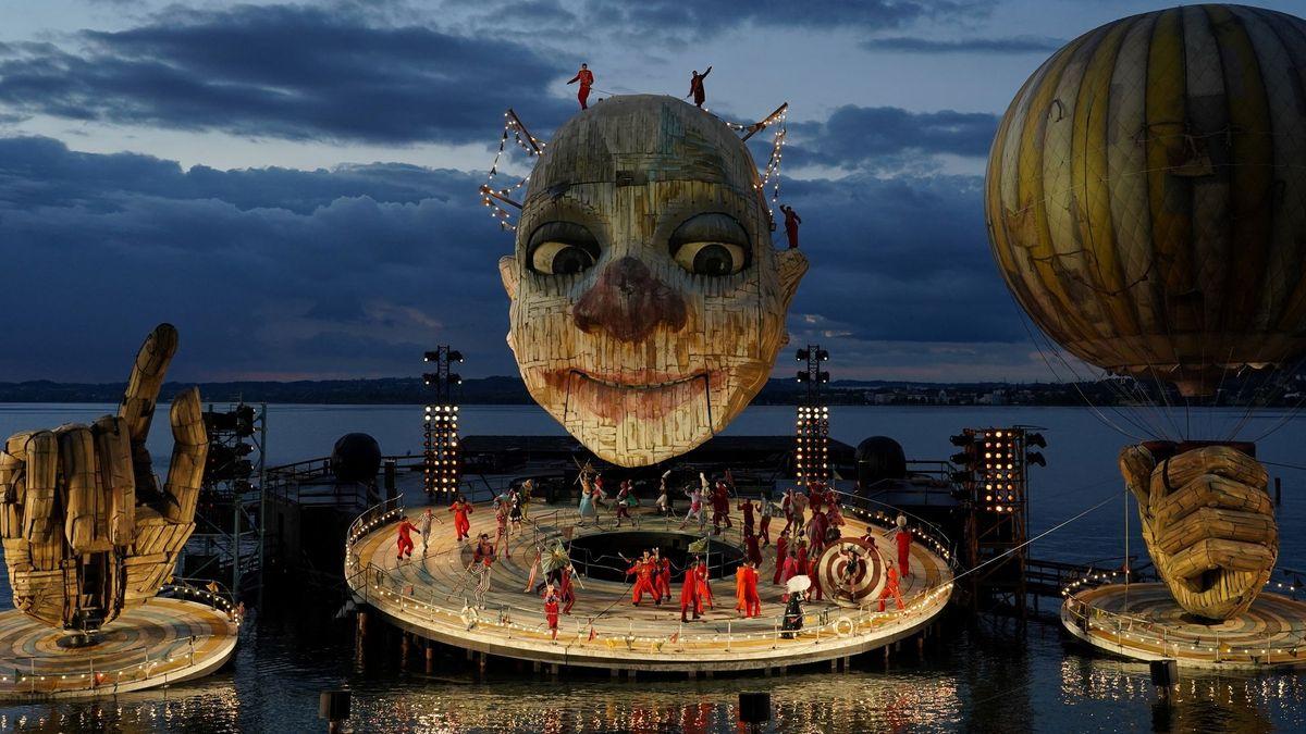 Chor und Statisten auf einer Scheibe und auf dem Kopf eines riesigen Clowns spielend