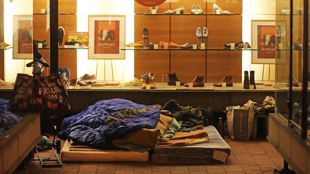 Ein Obdachloser schläft vor einem Geschäft.