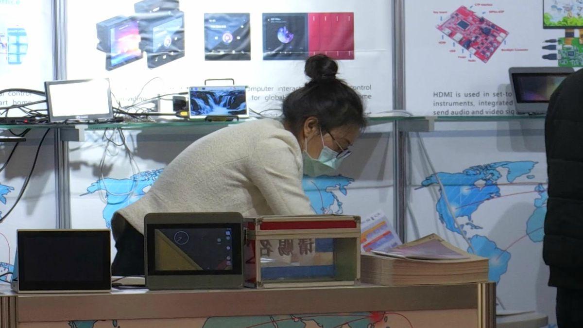 """Eine Ausstellerin der """"Embedded World"""" trägt einen Mundschutz, um sich vor dem Coronavirus zu schützen"""