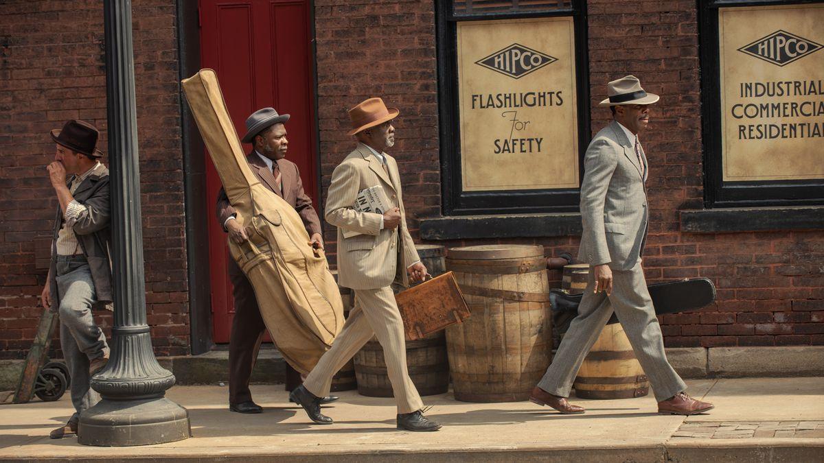 Drei schwarze Musiker im Outfit der 20erJahre gehen einen Gehweg entlang
