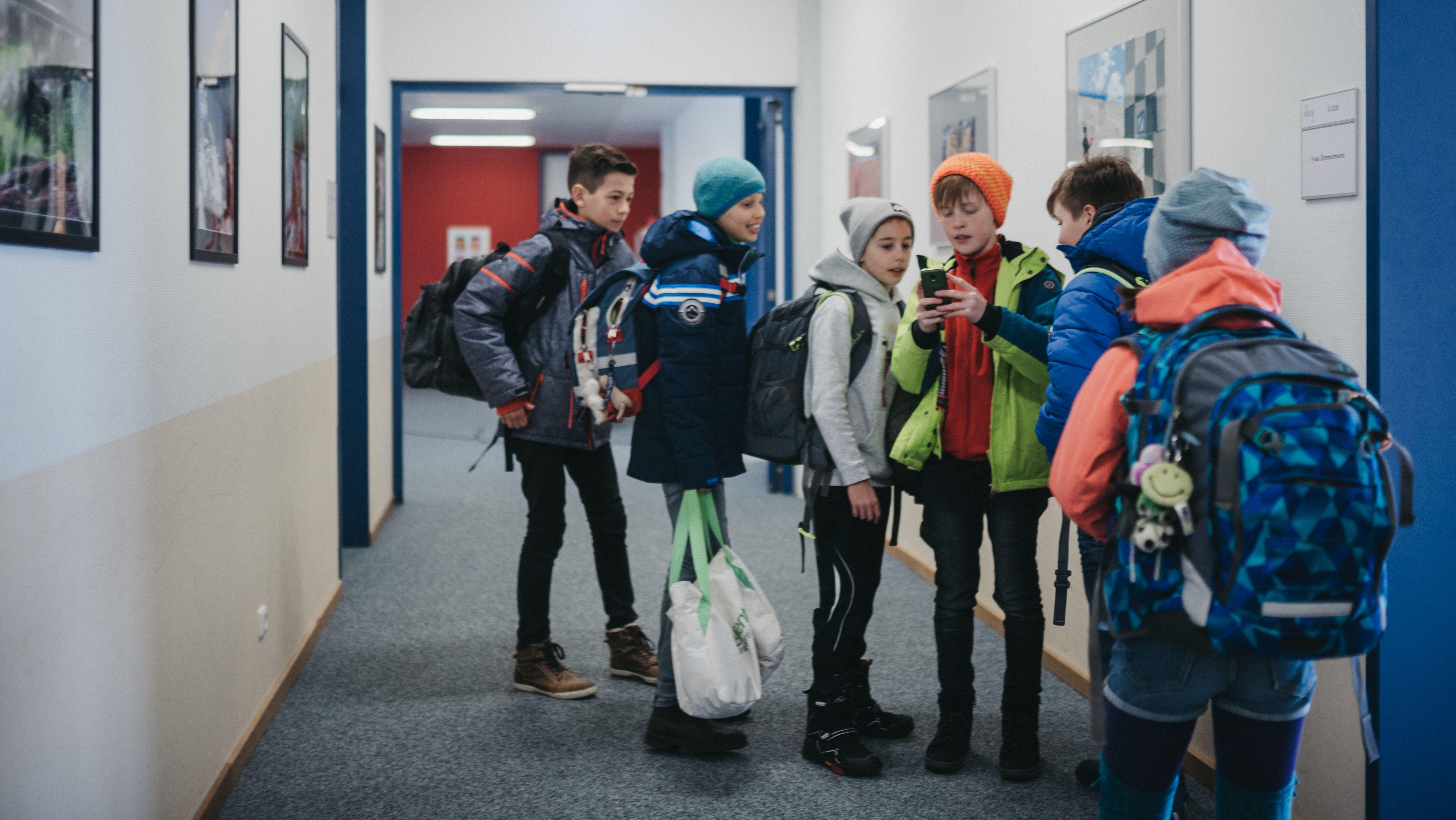Schüler, im Gang, mit einem Handy.