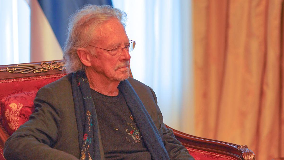 Der Schriftsteller sitzt in einem Paradesessel mit Schal um den Hals