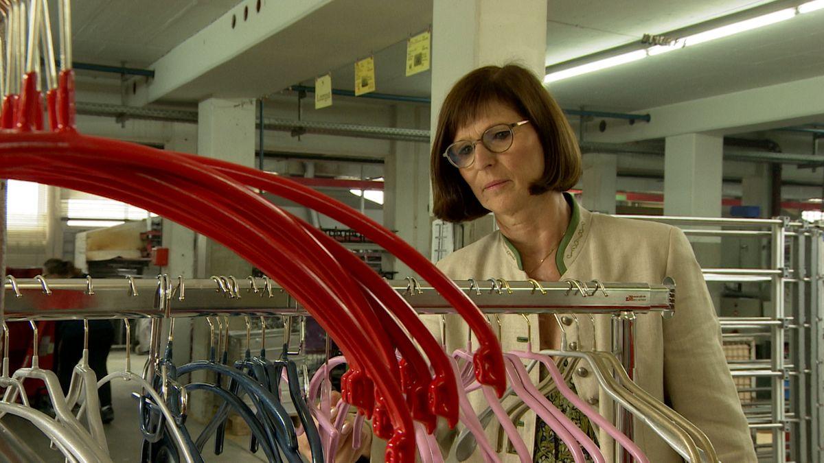 MAWA-Geschäftsführerin Michaela Schenk steht an Metall-Kleiderständern, auf denen Kleiderbügel in Rot, Glitzerrosa und Silber hängen.