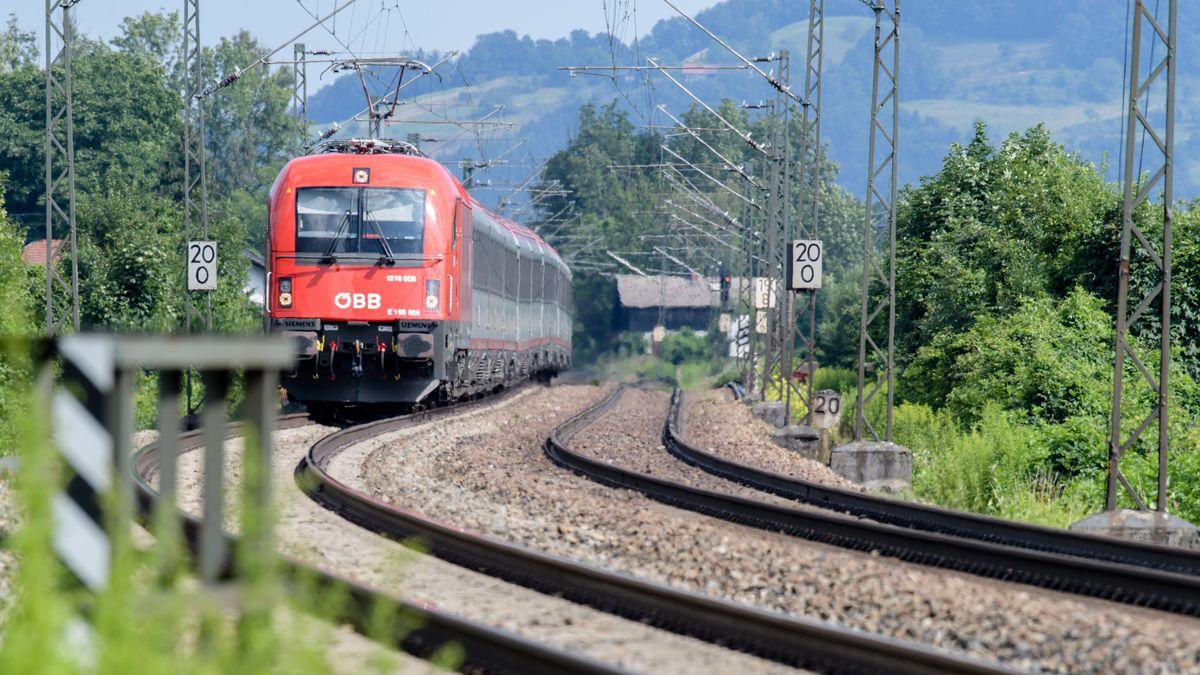 Zug der Österreichischen Bundesbahnen (ÖBB) fährt über die Gleise der Bahntrasse durch das Inntal zwischen Rosenheim und Kufstein.
