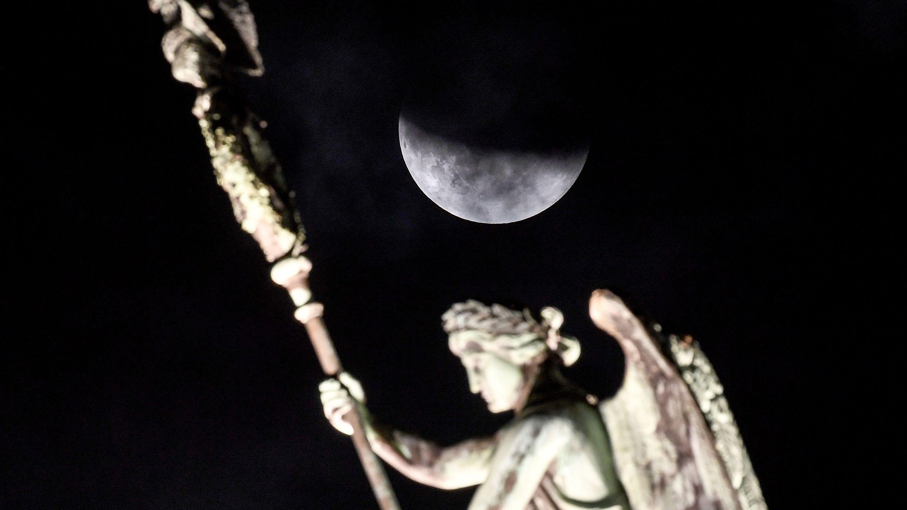 Berlin: Der Mond ist während einer partiellen Mondfinsternis hinter der Quadriga des Brandenburger Tors zu sehen.