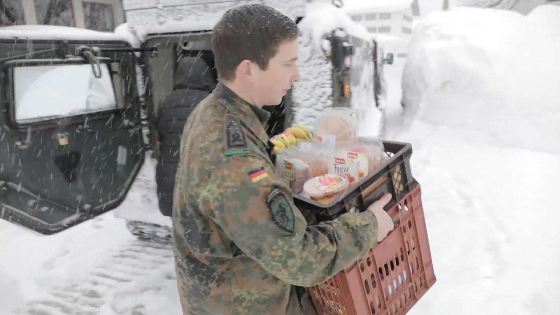 Ein Soldat der Bundeswehr trägt Körbe mit Lebensmitteln.