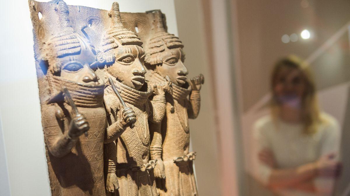 Besucherin betrachtet Skulptur mit drei Figuren in einer Vitrine