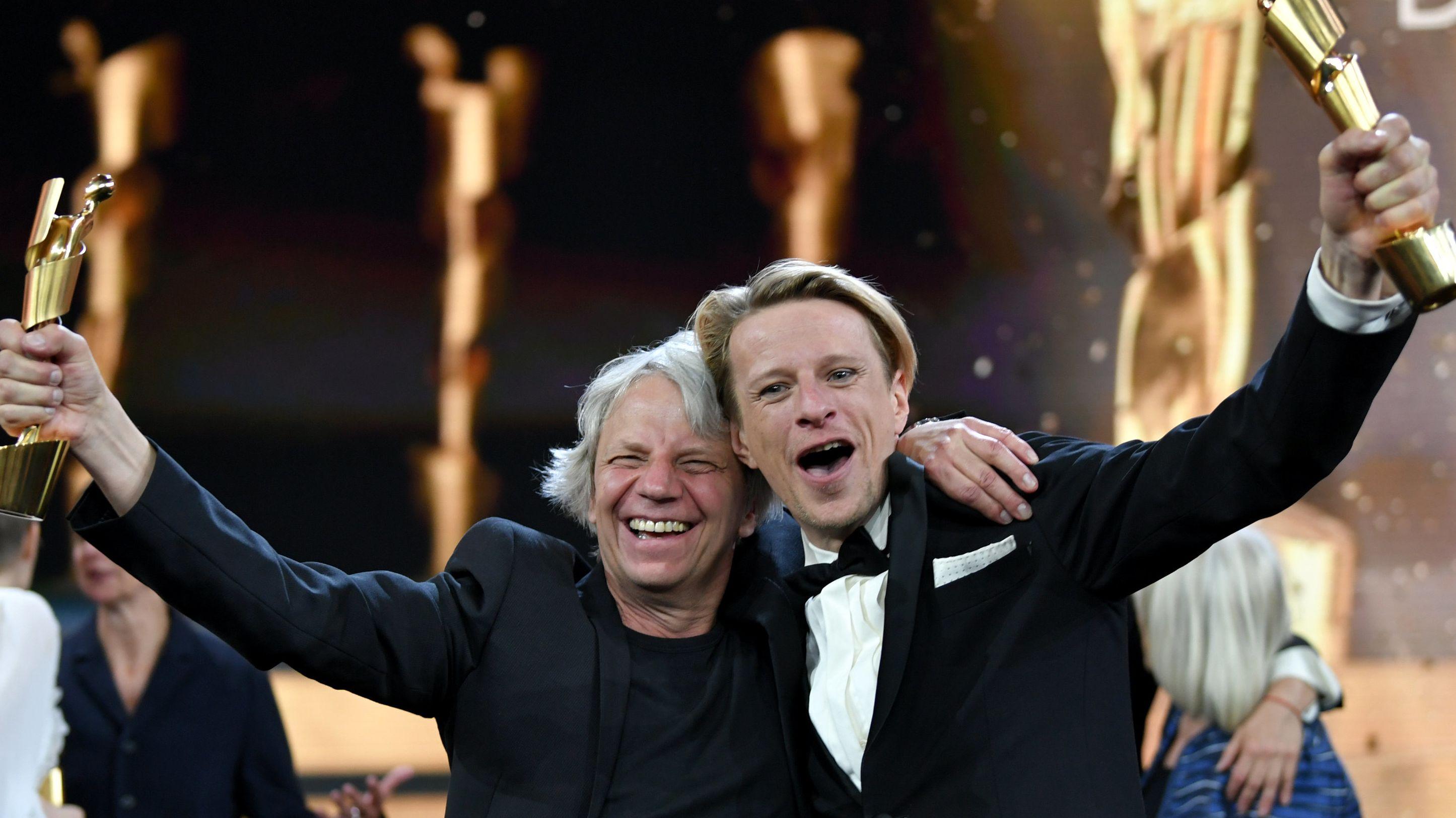 Zwei Männer halten Trophäen in der Hand und lächeln.