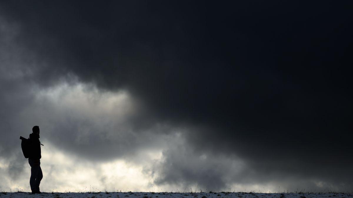 Ein Mann steht vor einem dunklen Himmel