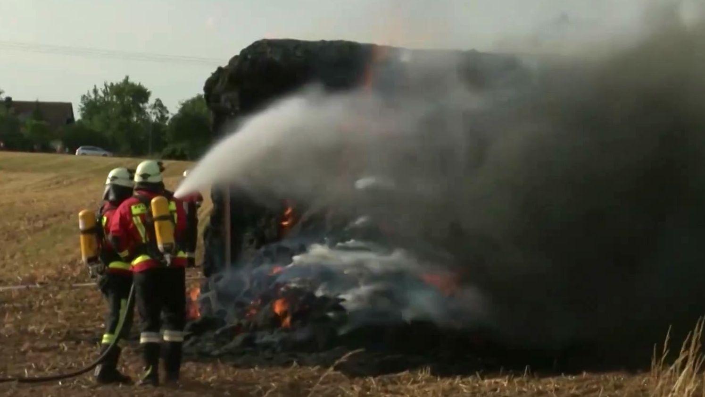 Feuerwehrleute löschen brennendes Stroh
