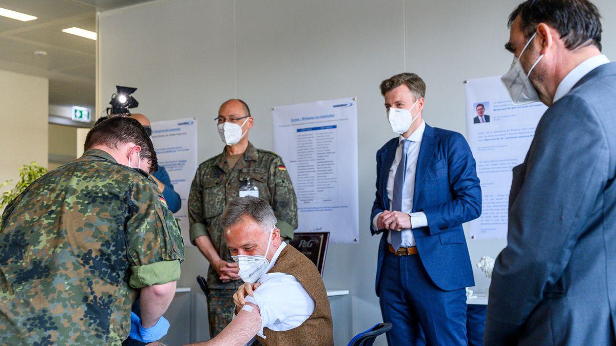 Bayerns Gesundheitsminister Klaus Holetschek sieht einem Mitarbeiter bei einer Betriebsimpfung zu.