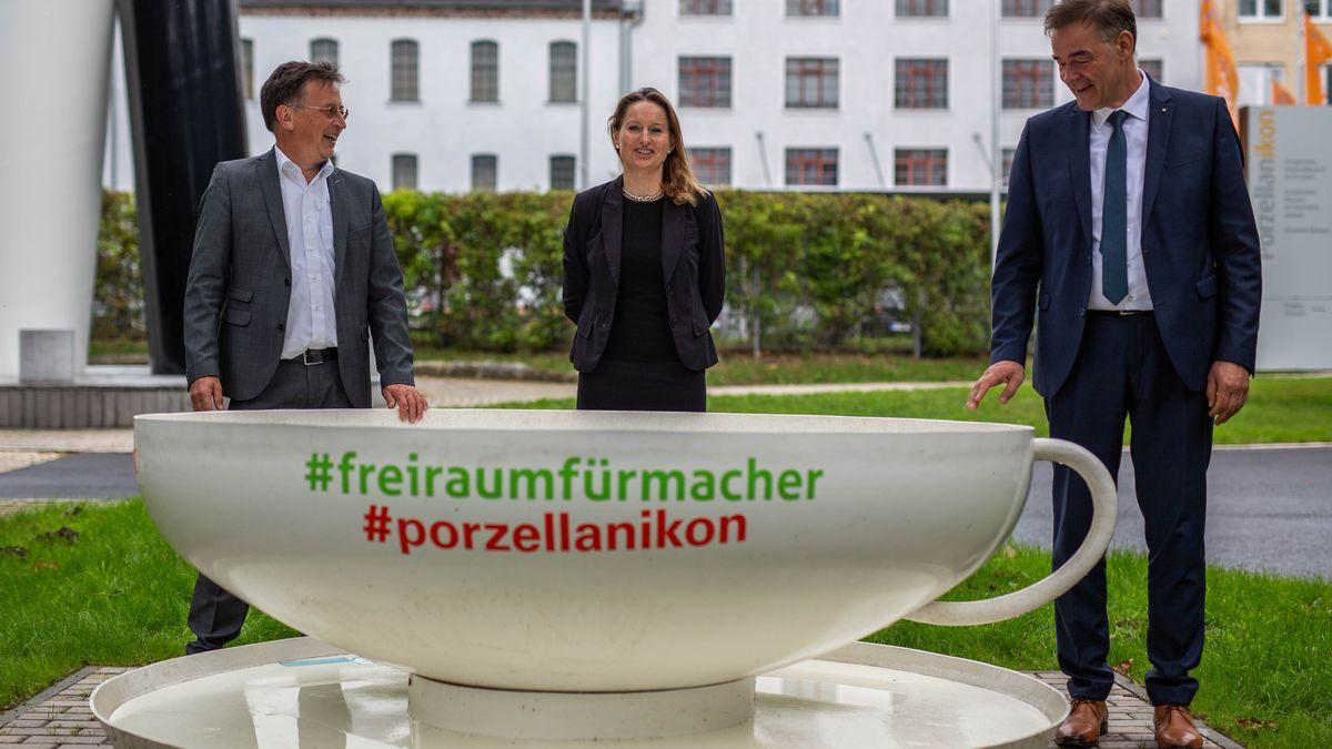 Vor dem Porzellanikon in Selb ist eine überdimensional große Tasse aufgestellt, dahinter stehen die Direktorin des Museums, Anna Dziwetzki, Tomas Edel, Leiter der Entwicklungsagentur Fichtelgebirge, und Peter Berek, Landrat des Landkreises Wunsiedel.