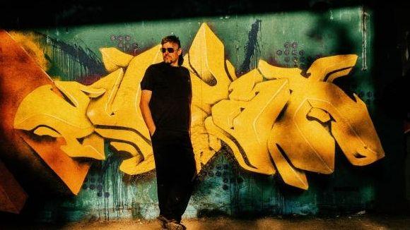 Johannes Enders mit Sonnenbrille vor einem knatschgelben Graffiti auf grüner Wand