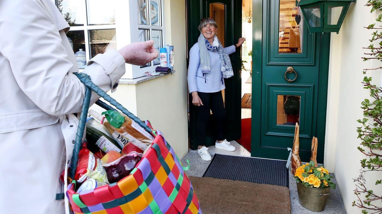 Eine Frau steht an einer Haustür. Davor eine andere Frau mit einer Einkaufstasche.